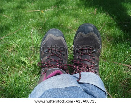 Feet of person sitting on grass, wearing blue jeans and sport boots - stock photo