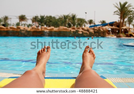 Feet of tanning woman at swimming pool in Egypt - stock photo
