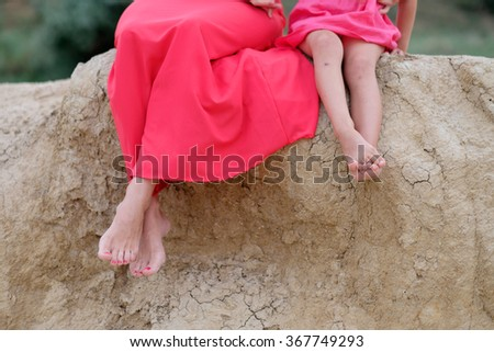 feet of the young mother with a baby in nature in a red dress - stock photo