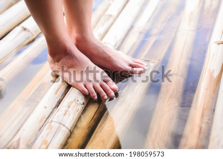Feet on bamboo in lake vintage colors  - stock photo