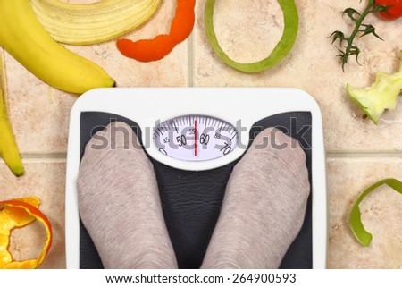 Feet on bathroom scale with fruit peals around  - stock photo