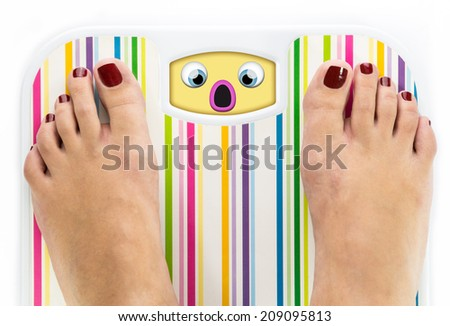 Feet on bathroom scale with scared cute face on dial - stock photo