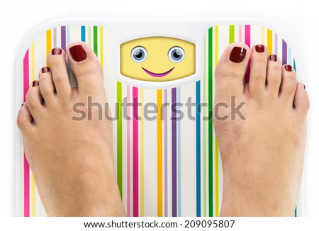 Feet on bathroom scale with smiling cute face on dial - stock photo