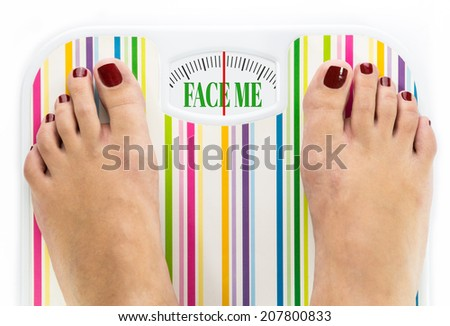 """Feet on bathroom scale with words """"Face me"""" on dial - stock photo"""