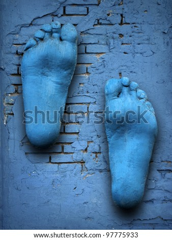 feet on old blue wall - stock photo
