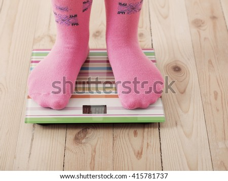 Feet on scales on wooden floor - stock photo