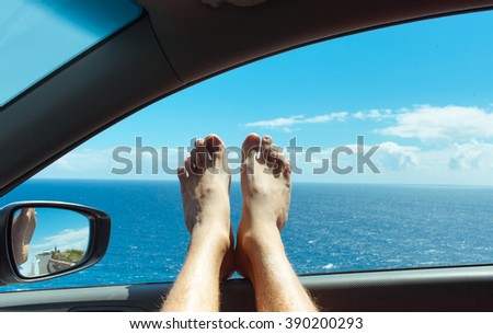 Feet relaxing in a car by the sea. (holiday/vacation concept) - stock photo