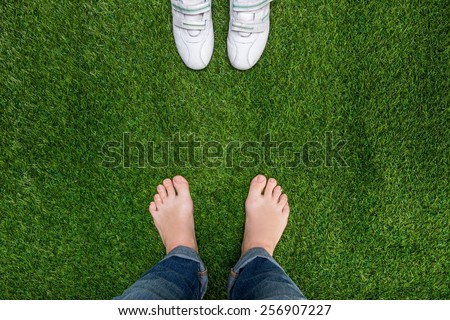 Feet resting on grass with sneakers standing opposit - stock photo