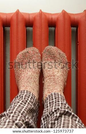 feet with wool socks warming on the radiator - stock photo