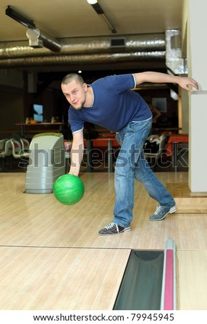Fellow planted oneself for throw of ball in bowling club - stock photo