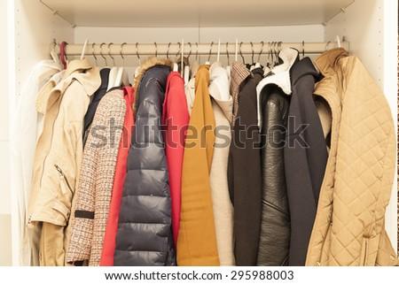 femal wardrobe with winter and summer jackets - stock photo
