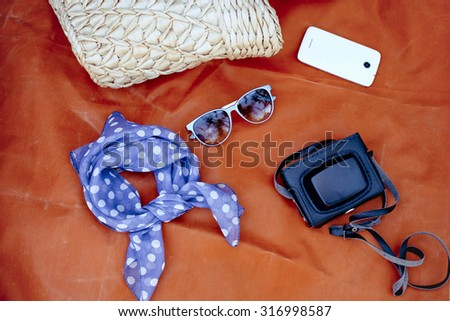 Female accessories: bag, scarf, sunglases, smartphone and came - stock photo