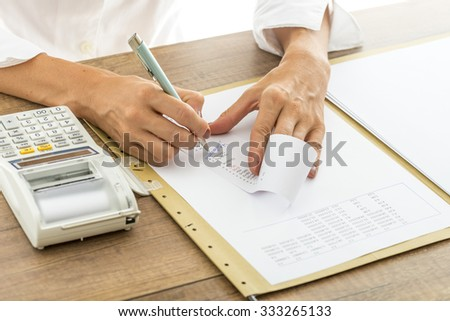 Female accountant calculating and reviewing numbers on a receipt as she crosses out numbers that do not match, with statistical report and adding machine on her desk. - stock photo