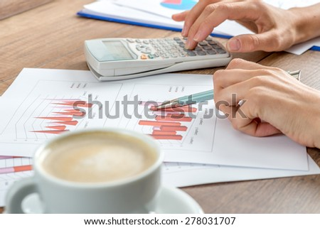 Female accountant working on a presentation or annual report analysing a set of graphs and charts with a manual calculator with a cup of coffee alongside. - stock photo