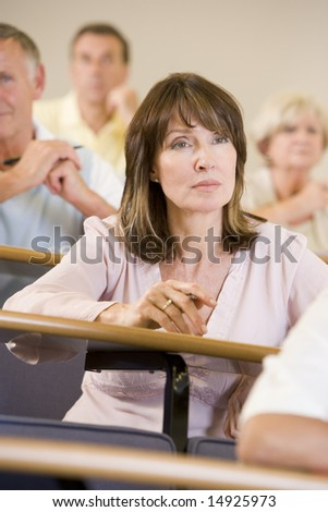 Female adult student listening to a university lecture - stock photo