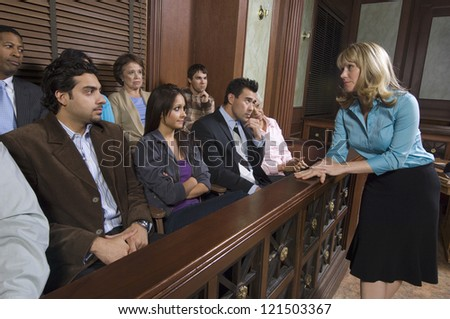 Female advocate talking to the jurors sitting in witness stand at courthouse - stock photo