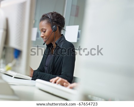 female african american customer service representative talking on the phone and typing on pc. Horizontal shape, side view, copy space - stock photo