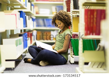 female african american student sitting on the floor reading a book in library - stock photo