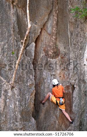 female alpinist climbing a rock - stock photo