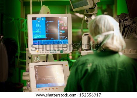 female anaesthesiologist at monitor in operation surgery room with green lights on - stock photo
