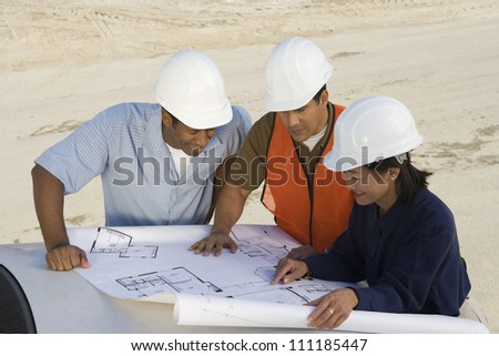 Female and male architects at construction site - stock photo