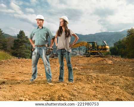 female and male colleagues engineers standing on construction site looking away - stock photo