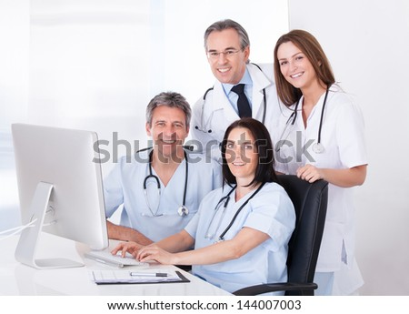 Female And Male Doctors Looking At Computer In Clinic - stock photo