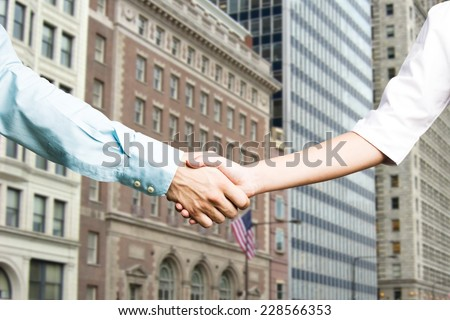 Female and male hands in handshake - Chicago buildings as a background - stock photo