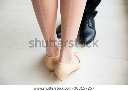 Female and male legs in rustic interior. Young woman dressed in cute white stockings with vertical line of little hearts drawing. Young couple in love standing together. - stock photo