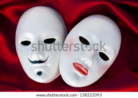 Female and male plaster masks on silk  fabric, close up - stock photo