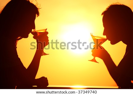 Female and man's silhouettes on sunset  drink from glasses - stock photo