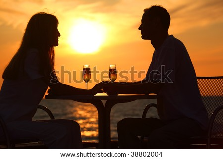 Female and man's silhouettes on sunset sit at table with two glasses outdoor, holding for hands - stock photo