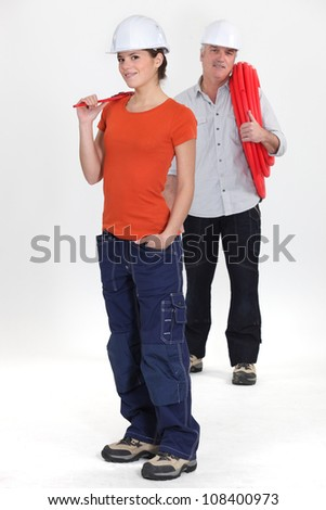 female apprentice and senior plumber - stock photo