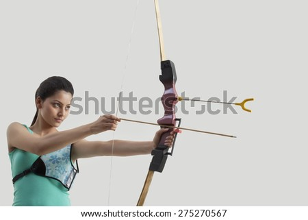 Female archer aiming bow and arrow against gray background - stock photo