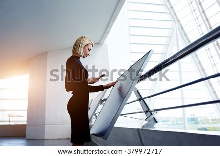 Female architect holding cell telephone while viewing 3d-visualization of project on digital touch screen, woman preparing a presentation for staff via high tech computer display and mobile phone - stock photo