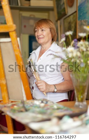 Female artist painting a picture on canvas with oil paints - stock photo