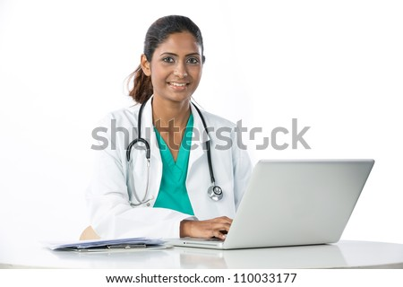 Female Asian doctor sitting at a table using a Laptop. - stock photo