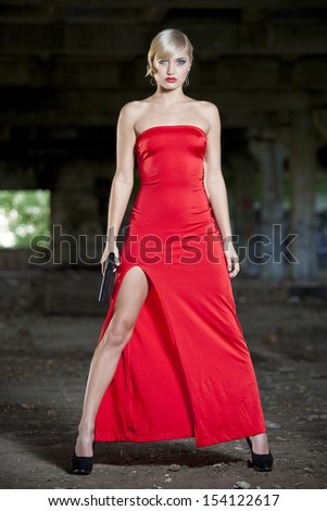 Female assassin in vintage look with gun in old fabric ruins - stock photo