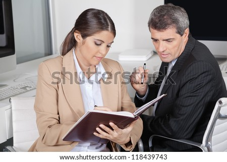 Female assistent checking appointments for manager in datebook - stock photo