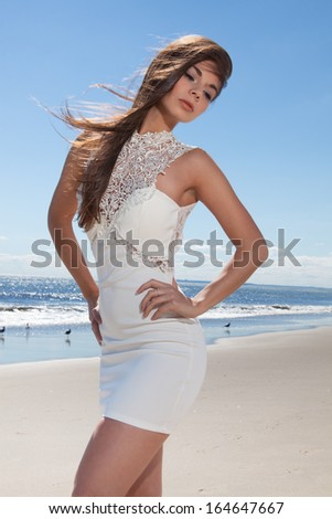 female at the beach with a white dress on - stock photo