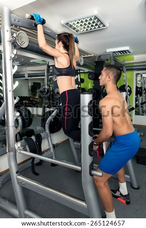Female Athlete Doing Pull Ups (Chin-Ups) in the Gym and trainer helping here. - stock photo