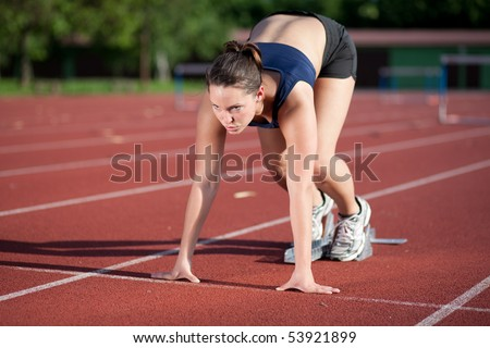Female athlete getting ready to blast off - stock photo