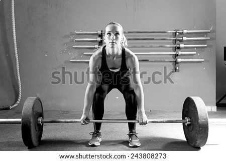 female athlete is preparing to lift deadlift at the gym - focus on the woman - stock photo