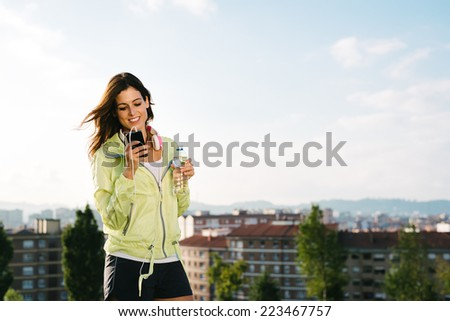 Female athlete messaging with smartphone while holding bottle of water. Fitness woman looking her cellphone or reading sms after exercising outdoor. - stock photo