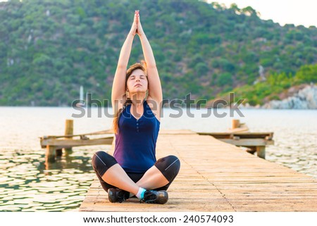 female athlete recovers breath on the pier - stock photo
