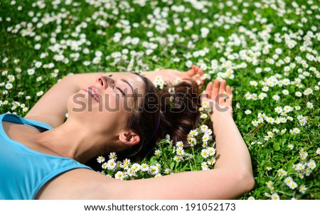 Female athlete resting and relaxing after workout. Relaxed joyful woman lying down on grass and spring flowers. Healthy lifestyle and happiness concept. - stock photo