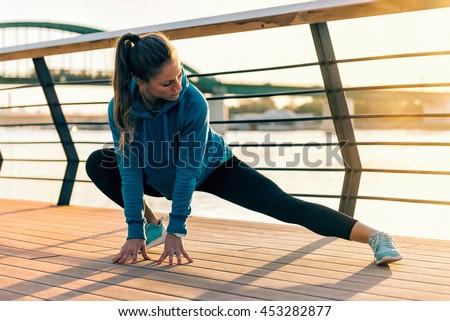 Female athlete streching outdoors - stock photo