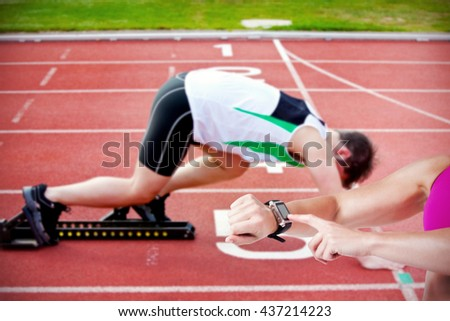 Female athlete using her smart watch against athletic man on the starting line putting his foot in the starting block - stock photo