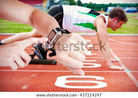 Female athlete using her smart watch against handsome sprinter on the starting line putting his foot in the s - stock photo