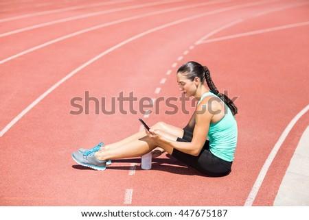 Female athlete using mobile phone on running track - stock photo